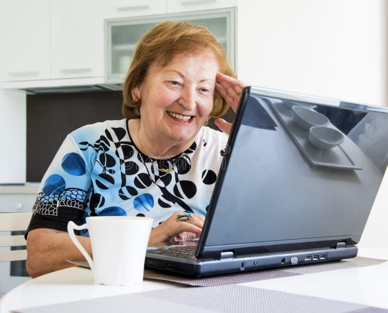 Une femme plus âgée avec un ordinateur images stock