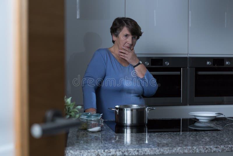 Une femme plus âgée dans la cuisine photo stock