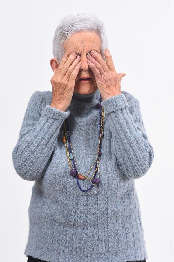 Une femme plus âgée faisant blesser ses yeux sur le fond blanc photo libre de droits