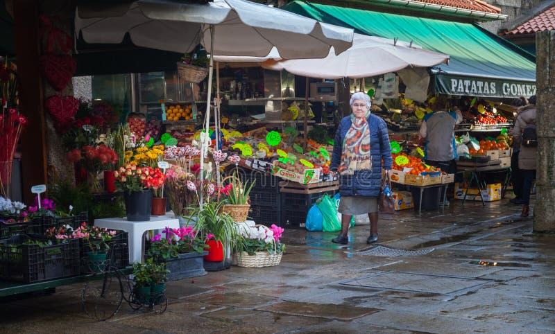 Une femme plus âgée marchant les stalles Différents genres de fleurs, Santiago de Compostela, Espagne photos libres de droits