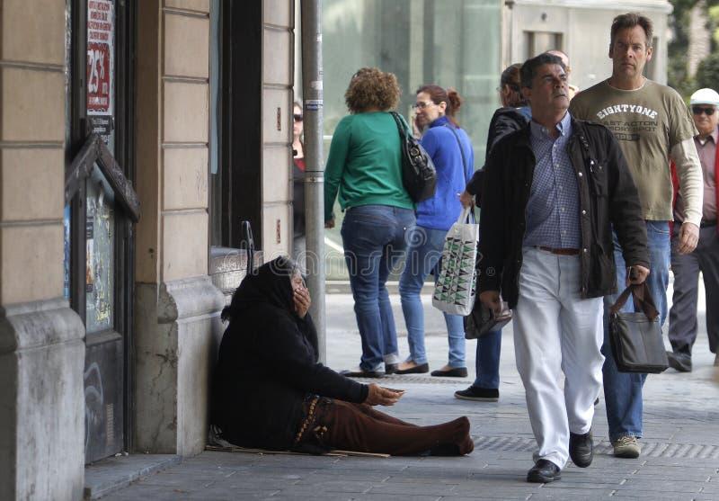Une femme plus âgée priant en centre ville photo stock