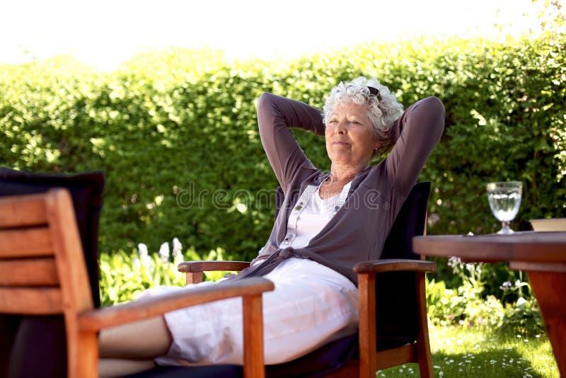 Une femme plus âgée se reposant dans le jardin d'arrière-cour photo stock
