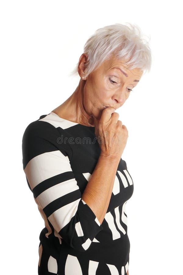 Une femme plus âgée semblant inquiétée et étourdie photographie stock libre de droits