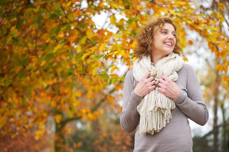 Une femme plus âgée souriant en automne photos stock