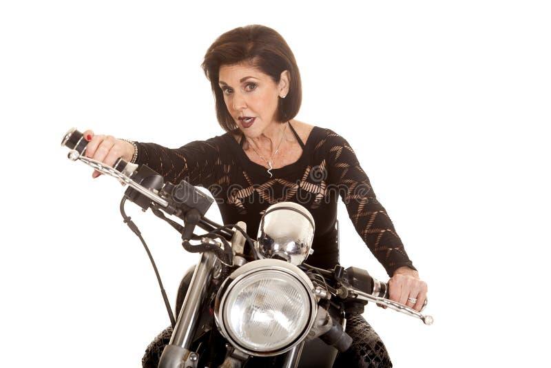 Une femme plus âgée sur l'entraînement de moto photographie stock