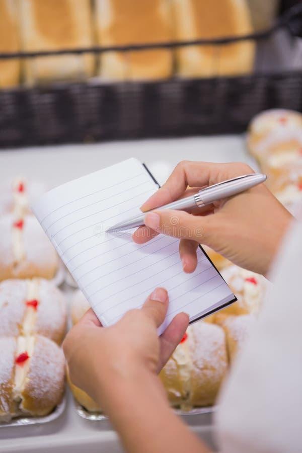 Download Une Femme Prenant Des Notes Au-dessus Des Pâtisseries Photo stock - Image du week, gâteau: 56489380