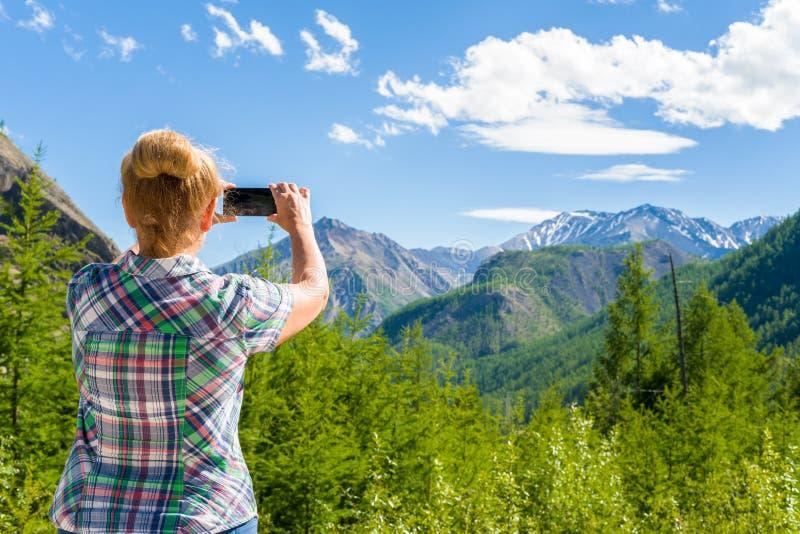 Une femme prend des photos du paysage Sayan oriental, Sibérie, Russie photos stock