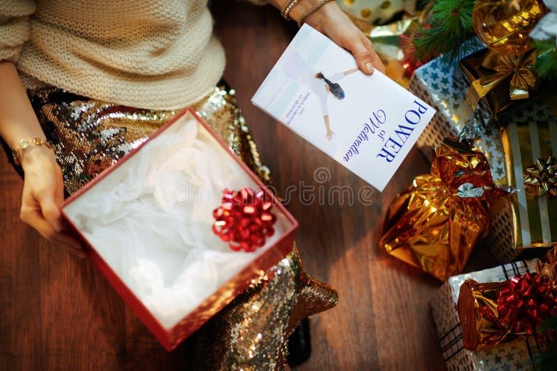 Une femme qui déballe les cadeaux de Noël et a un livre de motivation photo stock