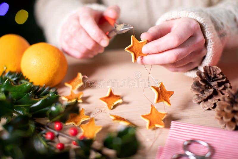 Une Femme Qui Fait Des Décorations Éco-Conviviales De Noël À Orange Peel photos libres de droits