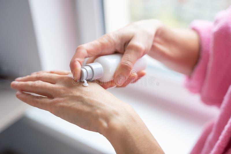Une femme qui met de la crème sur sa main photo de bouillon photos stock