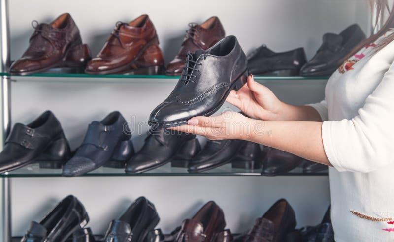 Une femme qui montre une chaussure mâle en cuir élégante dans le magasin image libre de droits