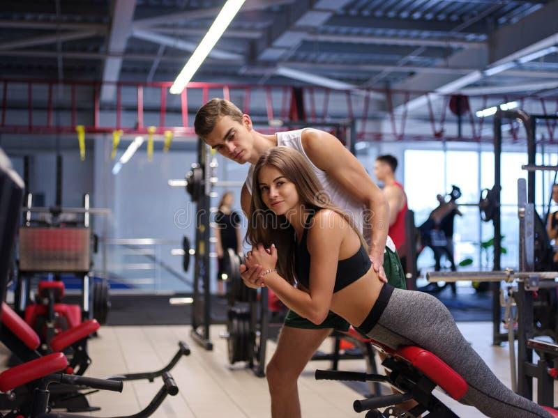 Une femme renversante faisant des exercices sur un simulateur sur un fond de gymnase Sport, forme physique, mode de vie et concep images libres de droits