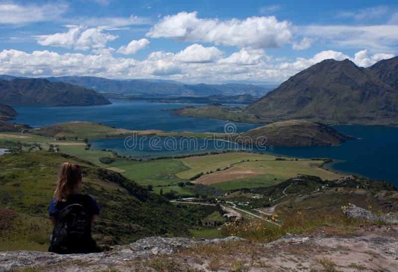 Une femme reposant et regardant le lac Wanaka près de la ville Wanaka au Nouvelle-Zélande image libre de droits