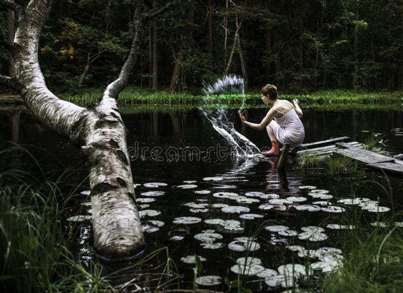 Une femme s'asseyant par un étang image libre de droits