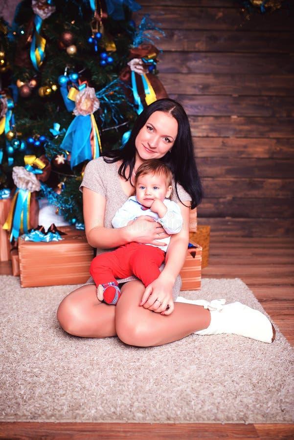 Une femme s'asseyant sur le plancher dans la chambre étreint doucement son fils photos libres de droits