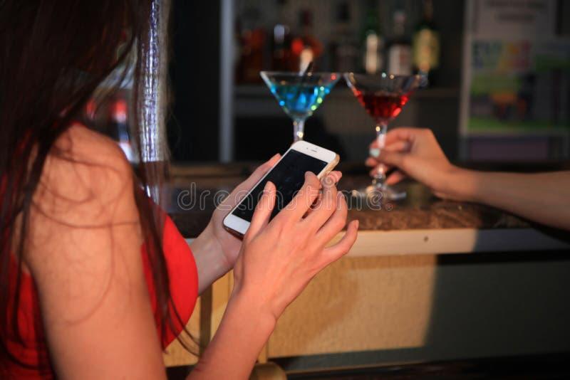 Une femme s'assied dans une boîte de nuit à la barre, et tient un téléphone portable image libre de droits