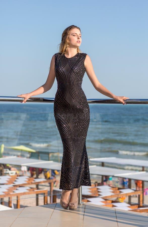 Une femme sûre dans une robe noire brillante sur un fond naturel bleu lumineux Vacances d'été photographie stock libre de droits