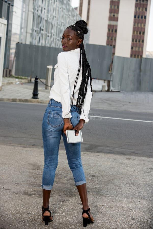 Une femme se tenant debout et tenant un smartphone photo stock