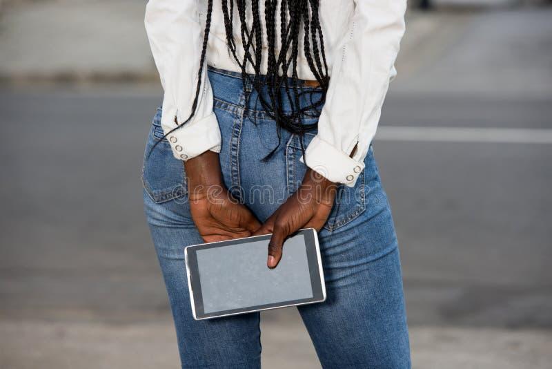 Une femme se tenant debout et tenant un smartphone photos libres de droits