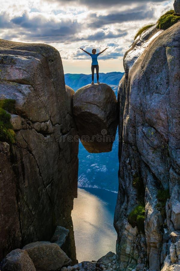 Une femme se tient au bord d'un stuc de Kjeragbolten de rocher photo stock