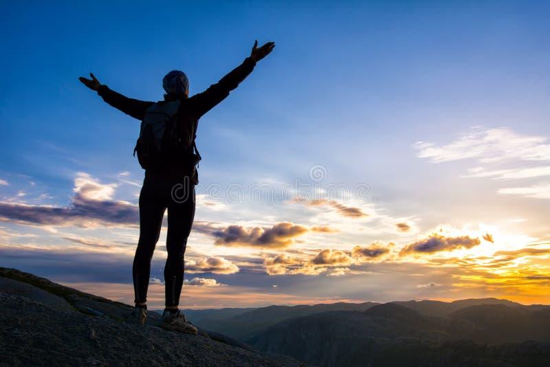 Une femme se tient au bord de la falaise sur le chemin au rocher photos stock