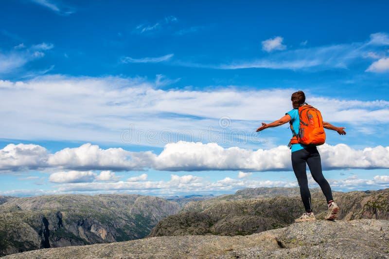 Une femme se tient au bord de la falaise sur le chemin au rocher images libres de droits