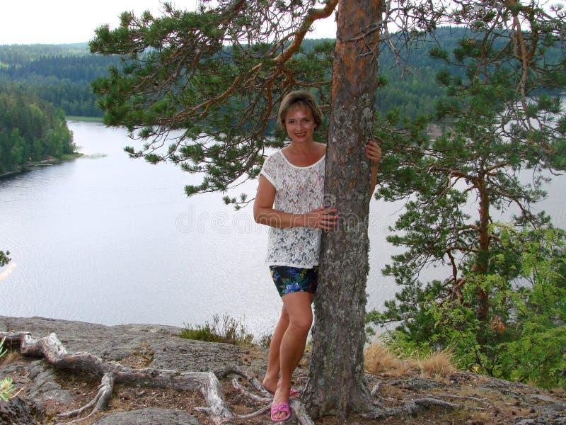 Une femme se tient près d'un arbre photo stock