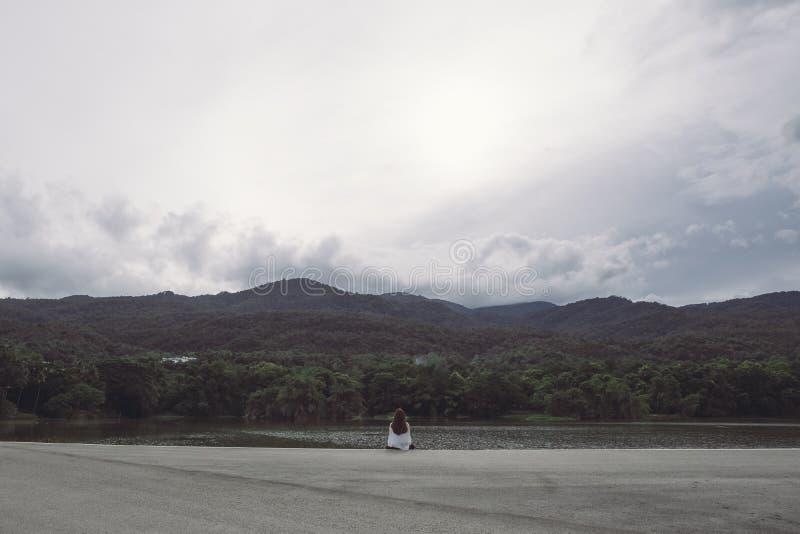 Une femme seul s'asseyant par le lac regardant les montagnes avec le ciel nuageux et sombre photo stock