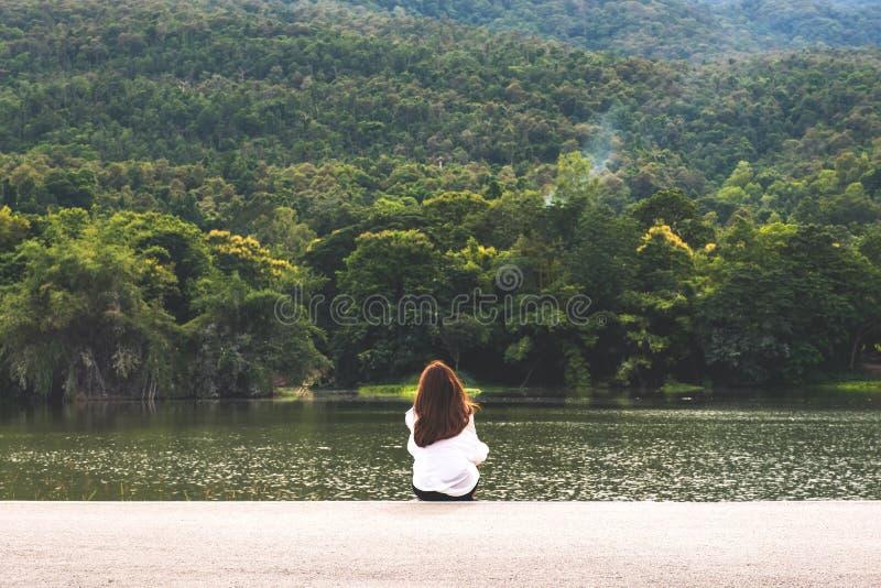 Une femme seul s'asseyant par le lac regardant les montagnes avec la nature nuageuse et verte photos stock