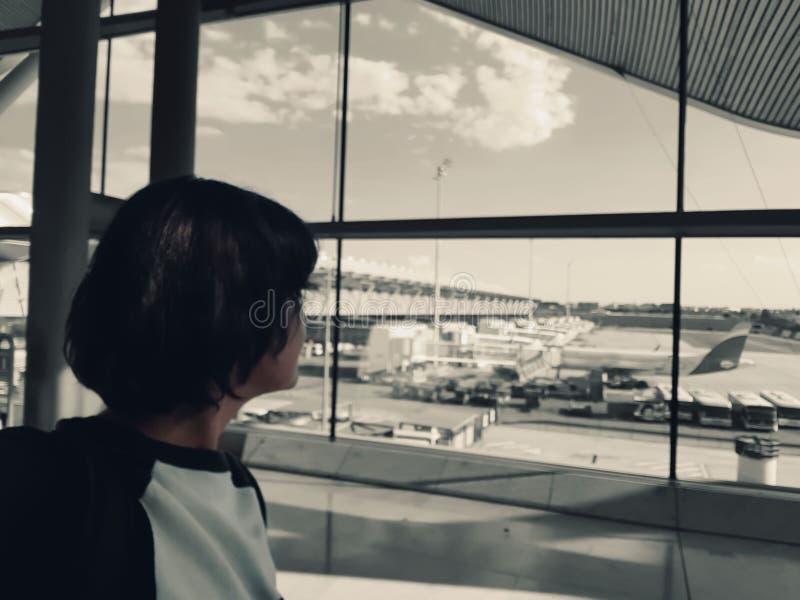 Une femme seule dans l'aéroport regarde le terrain d'atterrissage photos stock