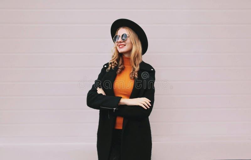 Une femme souriante élégante a croisé les bras en manteau noir, chapeau rond sur un mur gris photo stock