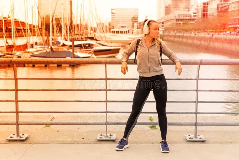 Une femme sportive écoutant de la musique à côté de la balustrade du pont photo stock
