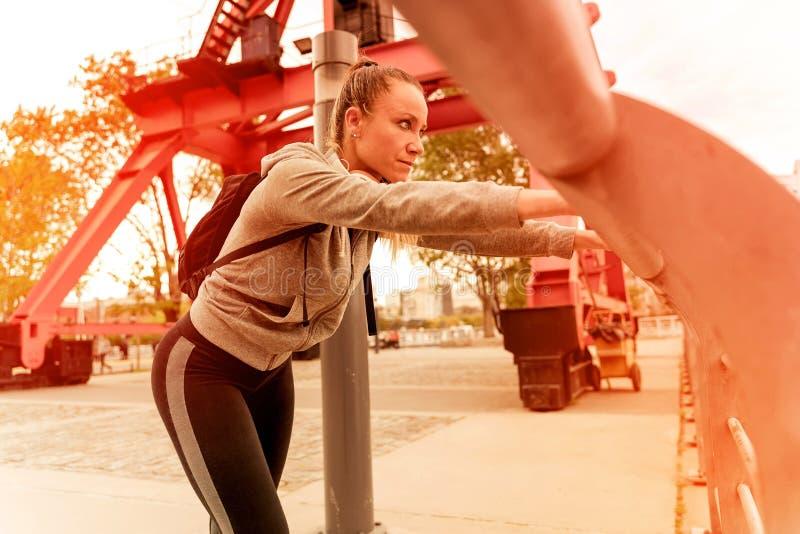 Une femme sportive se reposant et se penchant sur la balustrade du pont photos libres de droits