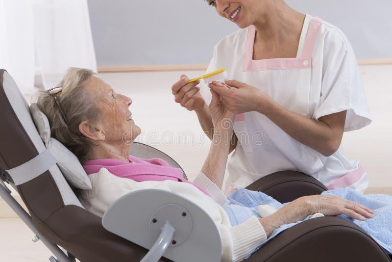 Une femme supérieure plus âgée recevant le hand'scare à la maison de traitement de beauté images stock