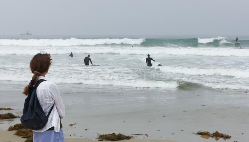 Une femme sur une plage observe des surfers photo stock