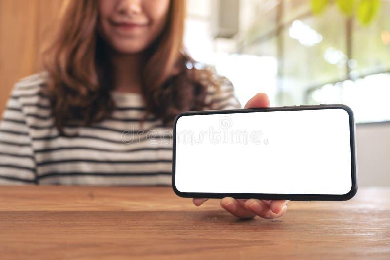 Une femme tenant et montrant le téléphone portable blanc avec l'écran vide horizontalement sur la table en bois image stock