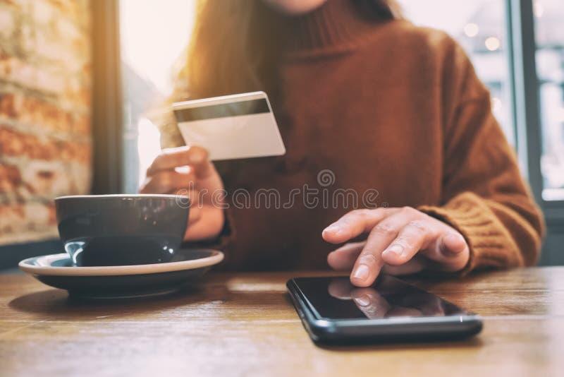 Une femme tenant la carte de crédit et se dirigeant au téléphone portable pour faire des emplettes en ligne photos stock