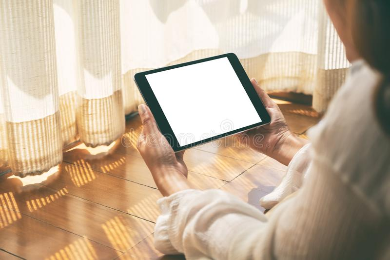 Une femme tenant le PC noir de comprim? avec l'?cran de bureau blanc de blanc horizontalement tout en fixant sur le plancher avec photo libre de droits