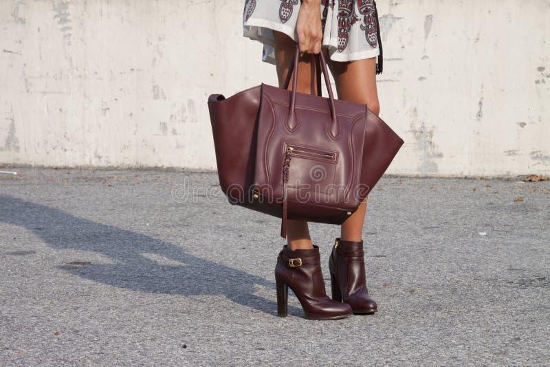 Une femme tenant un sac à main de concepteur et portant des butins image libre de droits