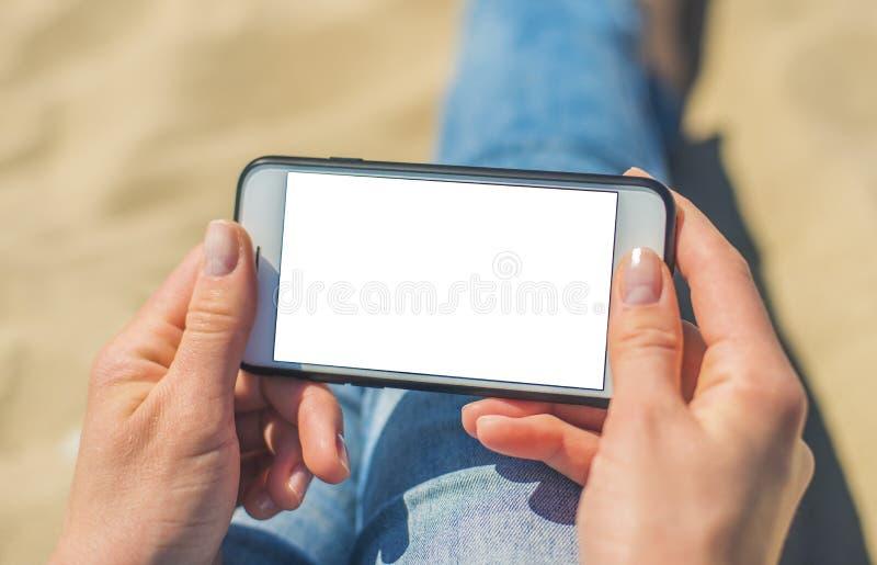 Une femme tenant un t?l?phone portable blanc avec un ?cran vide photographie stock libre de droits
