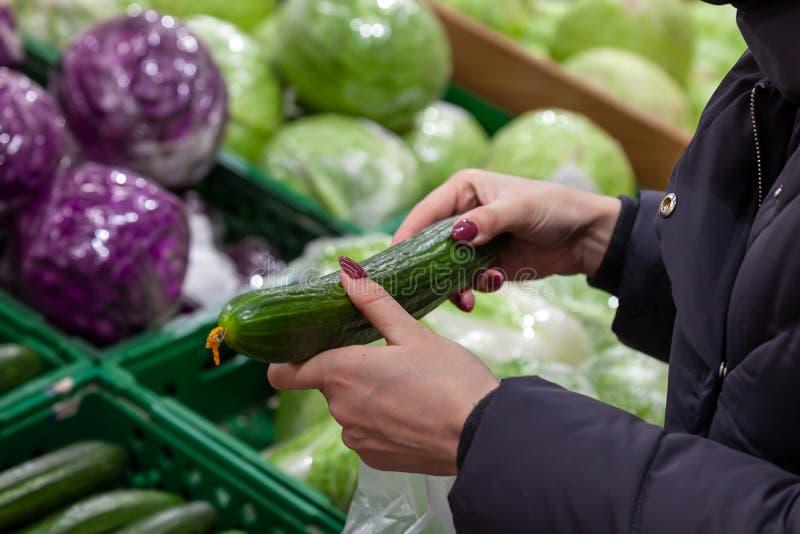 Une femme tient dans ses mains un long, lisse, vert concombre sur image stock