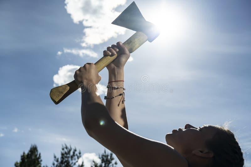 Une femme tient une hache dans des ses mains contre le ciel bleu, le soleil et les cimes d'arbre Concept d'égalité entre les sexe images stock