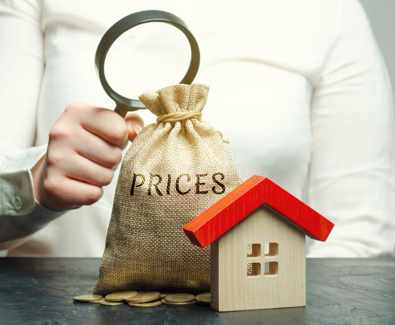 Une femme tient une loupe au-dessus d'un sac d'argent avec les prix de mot et une maison en bois Le concept de l'analyse des prix photos libres de droits