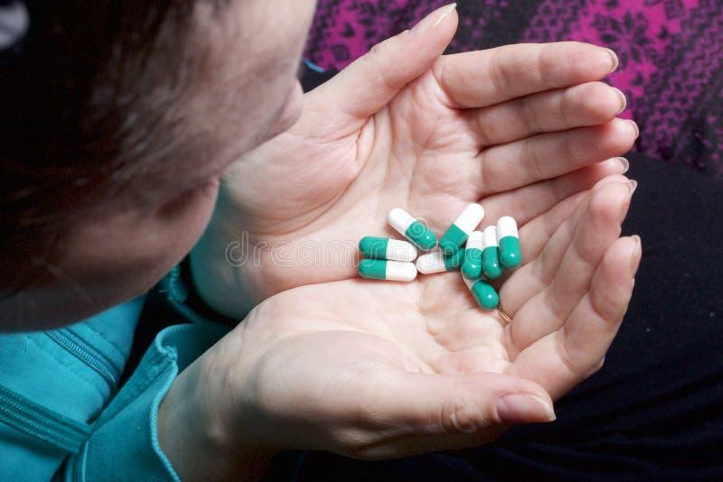 Une femme tient une poignée de pilules de couleur blanche et verte photos stock