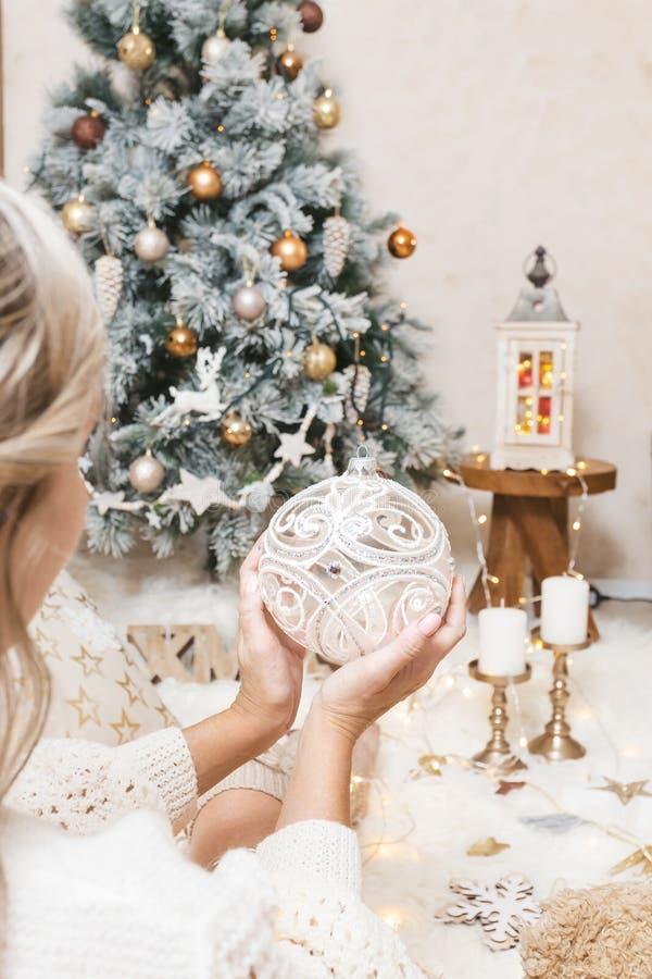 Une femme tient un bauble de Noël étincelant pour l'arbre photo libre de droits