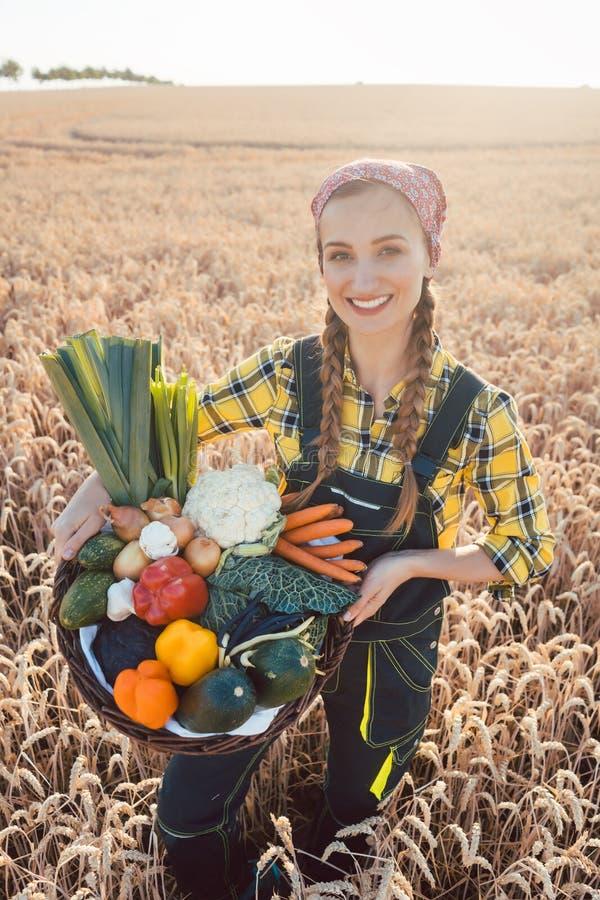 Une femme transportant une corbeille avec des légumes sains et produits localement photo libre de droits