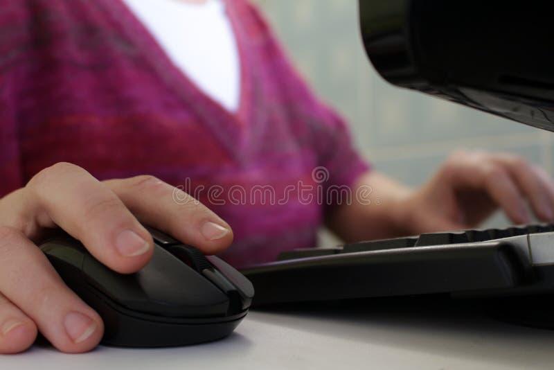 Une femme travaillant à un ordinateur Main sur la souris photographie stock libre de droits