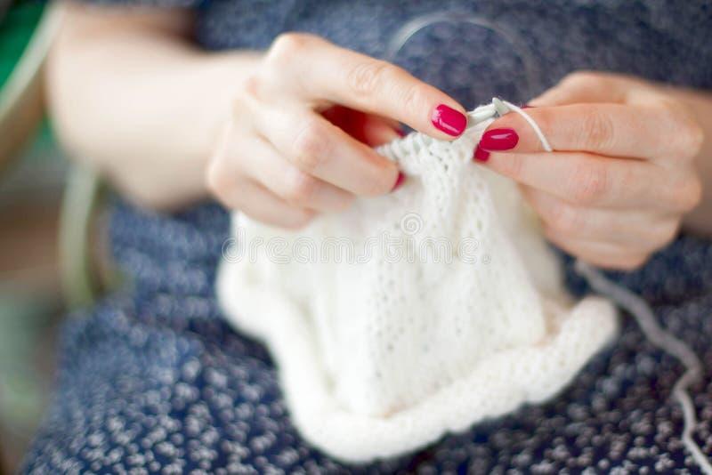 Une femme tricote une toile blanche avec des rais Remet le plan rapproché photographie stock libre de droits