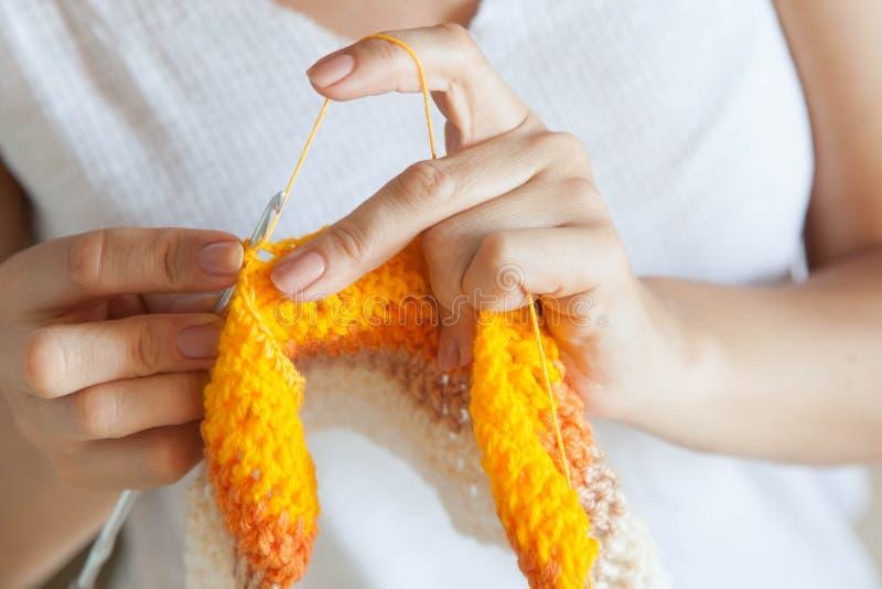 Une femme tricote un tissu coloré Remet le plan rapproché image libre de droits