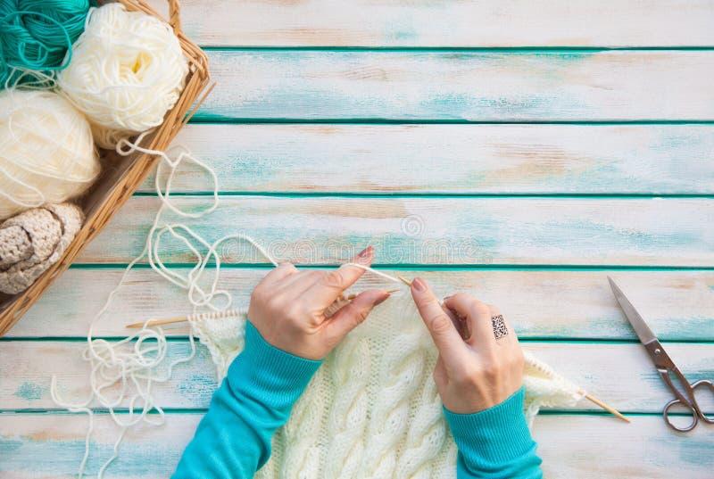 Une femme tricote un tissu tricoté par blanc de fil de laine Ne de tricotage photographie stock libre de droits
